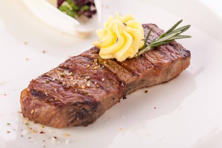 Tasty grilled beef steak topped with a twirled knob of butter and a sprig of fresh rosemary and served on a white plate, close up view photo
