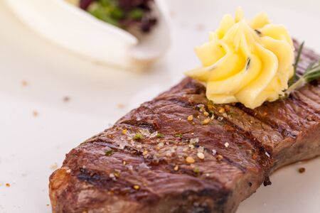 dollop: Tasty grilled beef steak topped with a twirled knob of butter and a sprig of fresh rosemary and served on a white plate, close up view