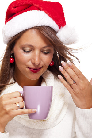 Cold attractive young woman with a cute smile in a festive red Santa hat sipping a hot mug of coffee did she is cradling in her hands to warm up in the winter weather, on white photo