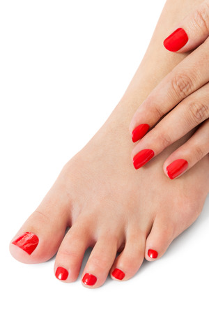 toenails: Woman with beautiful neatly manicured finger and toenails red sitting with bare feet clasping her ankles to display her nails, closeup on white in a fashion and beauty concept