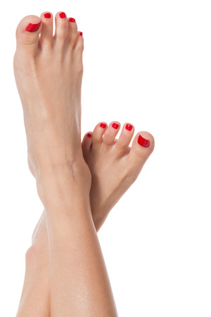 feet crossed: Sexy slender female feet with care fully pedicured fashionable red nails Displayed in the crossed position on white with copyspace Stock Photo
