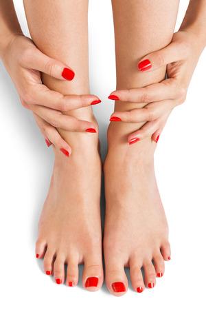 Mujer con hermosa dedo perfectamente cuidados y uñas de color rojo sentado con los pies descalzos juntando sus tobillos para mostrar sus uñas, detalle en blanco en un concepto de moda y belleza