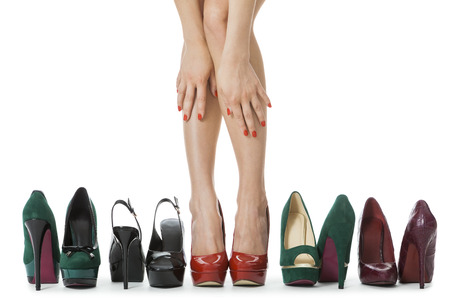 shapely legs: Close up Flawless Woman Legs in Glossy Red High Heel Shoes Standing Between Other Elegant High Heels. Isolated on White Background.