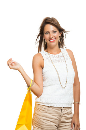 gift spending: Very Happy Stylish Woman Raising Three Colored Shopping Paper Bag with Mouth Open and Looking at the Camera. Isolated on White Background.