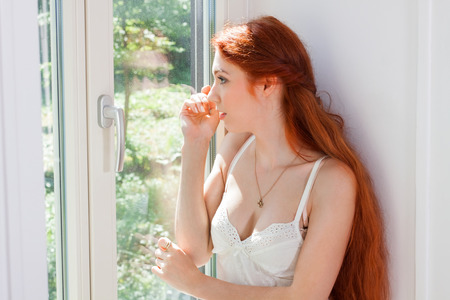 reverie: Thoughtful Pretty Young Woman with Long Blond Hair, Wearing White Night Wear, Sitting at the Glass Window While Looking Into Distance at Early in the Morning. Stock Photo