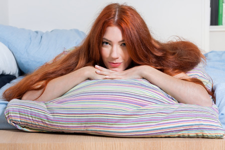 respite: Close up Pretty Blond Woman Leaning on her Hand on Top of a Colored Pillow While Lying on her Stomach and Looking at the Camera. Stock Photo