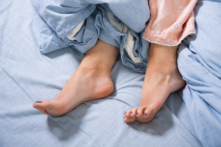 Close up Bare Feet of a Young Woman Lying Down on a Blue Bed, Captured in High Angle View.