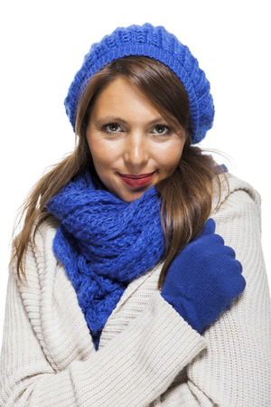 close knit: Close up Pretty Smiling Young Woman Wearing Winter Knit Outfit with Blue Bonnet, Scarf and Gloves. Captured in Studio with White Background While Looking at the Camera.