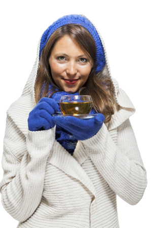 ensemble: Fashionable young woman in a blue knitted winter ensemble and cowl neck jersey sipping a cup of hot tea with a smile in an effort to keep warm, isolated on white Stock Photo