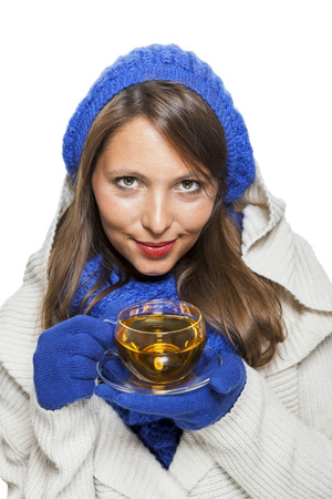 cowl: Fashionable young woman in a blue knitted winter ensemble and cowl neck jersey sipping a cup of hot tea with a smile in an effort to keep warm, isolated on white Stock Photo
