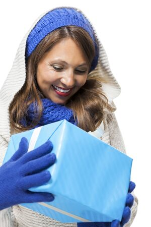pleased: Young woman in fashionable blue knitted winter fashion accessories holding a matching blue gift in her hands looking down at it with a pleased smile, isolated on white Stock Photo