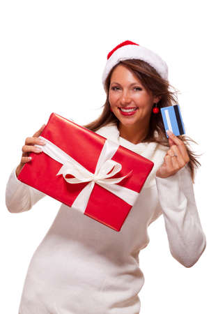 shopping spree: Attractive woman with a lovely smile wearing a red Santa hat holding a big red Christmas gift box and bank card as she celebrates her successful shopping spree Stock Photo