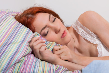 somnolent: Close up Attractive Young Blond Woman Sleeping on her Bed Tightly While Lying on her Side Position.