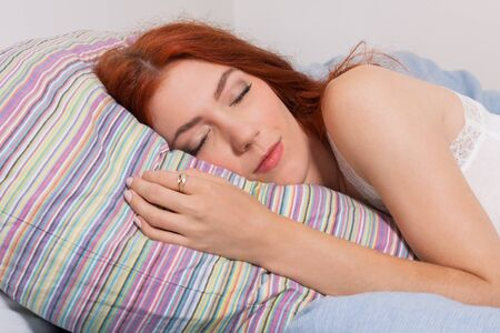 slumbering: Close up Attractive Young Blond Woman Sleeping on her Bed Tightly While Lying on her Side Position.