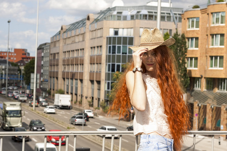 downcast: Gorgeous Woman in Hat with red hair on Cloudy Sky background Stock Photo