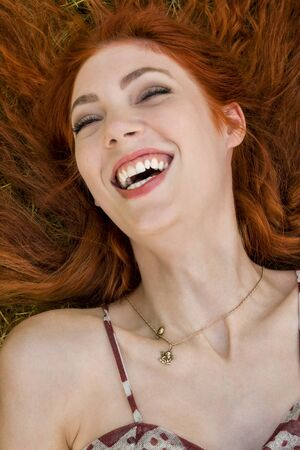 fanned: Close up Very Happy Young Woman Lying on Grassy Ground Stock Photo