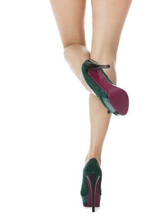 tantalizing: Close up Sexy Flawless Woman Legs in Green High Heel Shoes with One Leg Lifted and Crossing the Other Leg. Isolated on White Background. Stock Photo