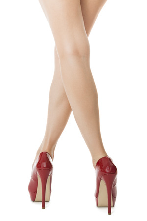 tacones rojos: Flawless mujer en las piernas elegantes zapatos rojos del alto talón, aislado sobre fondo blanco.
