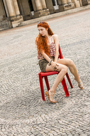 Close up Pretty Young Blond Woman, in trendy Attire, Sitting on Red Chair While Looking at the Camera. Stock Photo