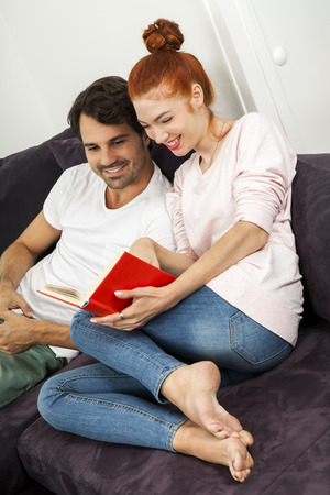 barefoot man: Young Couple Resting on the Sofa at the Living Room While the Man is Watching TV and Woman is Reading a Book.
