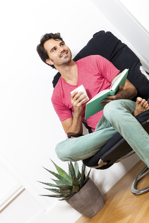 immersed: Young Man in Casual Clothing Sitting on Black Chair While Reading a Book and Holding a Glass of Drink.