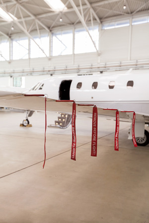 hangar: Airplane in Hangar with remove before flight Labels in red warning safety