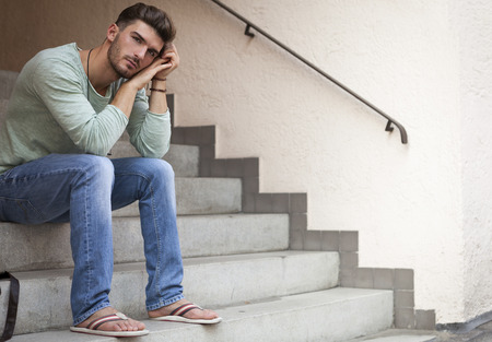 dejected: Casual  handsome young man with a beard sitting on cement steps with his head resting on his hand and a serious dejected expression Stock Photo