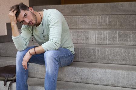 bel homme: Casual beau jeune homme avec une barbe assis sur les marches de ciment, la t�te appuy�e sur sa main et une expression morne grave Banque d'images