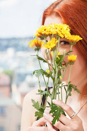 musing: Close up Thoughtful Pretty Young Woman Holding Yellow Flowers, Looking Outside While Leaning on Glass Window.