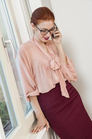 dudando: Cierre de Grave Mujer Bonita Oficina de visita elegante Vestimenta Mirando Afuera por la ventana de cristal Foto de archivo