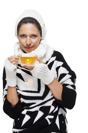 mitts: Elegant woman in a stylish black and white winter outfit with matching white mitts, scarf and knitted hat drinking a cup of hot tea, isolated on white