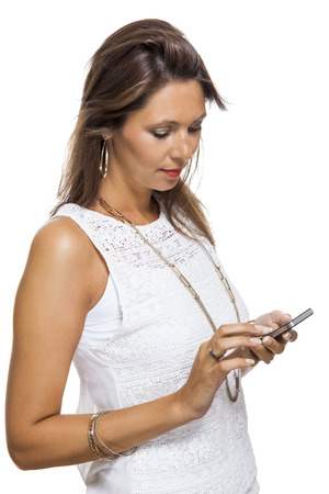 flicking: Vivacious attractive woman reacting to a text message on her mobile phone flicking her hair in the air and staring at the phone with her mouth open, on white with copyspace Stock Photo