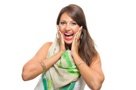 Close-up zeer gelukkige jonge vrouw, die trendy wit overhemd met Scarf Outfit, raken haar gezicht met haar twee handen terwijl u op de camera. Geïsoleerd op wit.