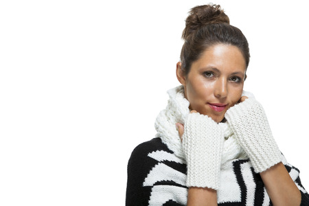 downcast: Attractive elegant woman in winter fashion snuggling down into her white scarf and black and white jumper to ward off the cold winter weather, on white Stock Photo