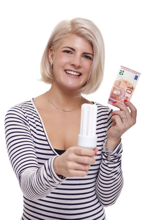 saving electricity: Woman holding an eco-friendly light bulb with a 10 Euro banknote threaded through it in a conceptual image of efficiency and savings
