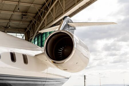 private jet: Close up of the engine housing on a small twin-engine corporate passenger jet parked in a hangar at an airport Stock Photo