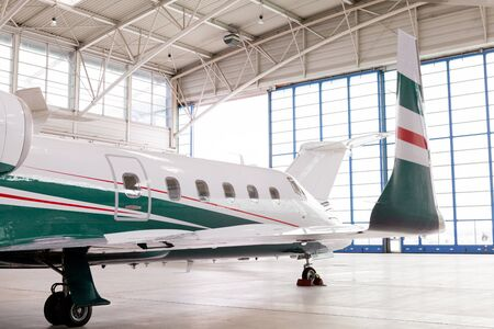 corporate jet: Small private corporate jet with green, red and white markings parked in a hangar at an airport, close up angled view of the nose and fuselage in an aviation, transport and travel concept