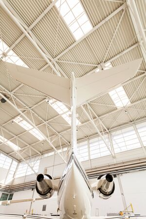 skylights: Low Angle View of Small Passenger Airplane Tail Inside Brightly Lit Hangar with Skylights