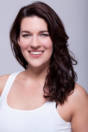 cabello negro: atractiva mujer sonriente con una hermosa sonrisa c�lida y el hombro la longitud del cabello rizado mirando a la c�mara sobre un fondo gris