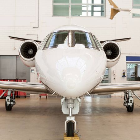 angled view: Small private corporate jet with green, red and white markings parked in a hangar at an airport, close up angled view of the nose and fuselage in an aviation, transport and travel concept