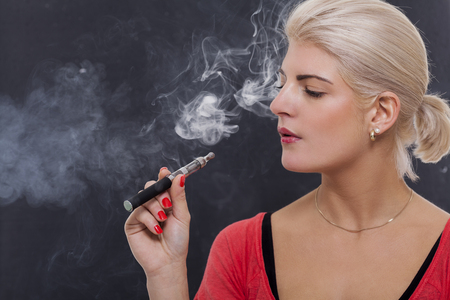Stylish blond woman smoking an e-cigarette exhaling a cloud of smoke with her eyes closed in enjoyment, profile view on a dark background Фото со стока