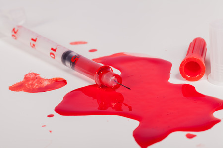 intramuscular: High Angle View of Syringe Needle Squirting Red Liquid or Blood onto White Background in Studio Still Life - Concept Image