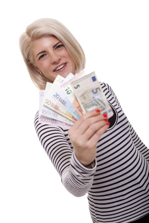 denominational: Attractive smiling blond woman holding up a handful of fanned Euro notes in different denominations, tilted angle conceptual image isolated on white