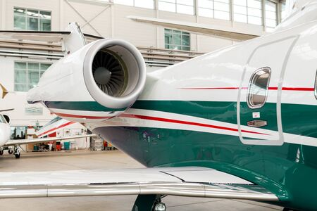 fuselage: Small private corporate jet with green, red and white markings parked in a hangar at an airport, close up angled view of the nose and fuselage in an aviation, transport and travel concept