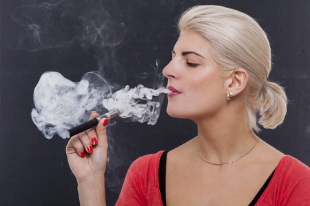 persona fumando: Mujer rubia con estilo que fuma un cigarrillo electr�nico exhalando una nube de humo con los ojos cerrados en el disfrute, vista de perfil sobre un fondo oscuro Foto de archivo