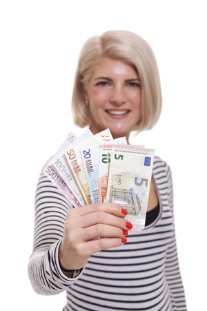 Attractive smiling blond woman holding up a handful of fanned Euro notes in different denominations, tilted angle conceptual image isolated on white