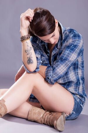 sexy boots: Beautiful single woman in western style boots, jeans shorts and blue flannel shirt with tattooed arm sitting over gray background