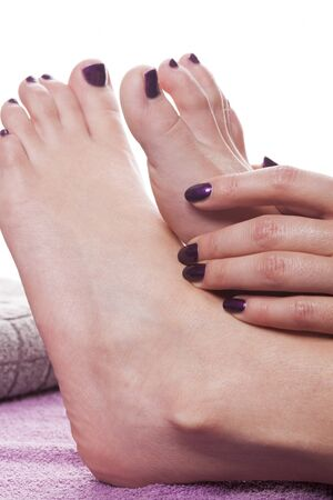 manicured hands: Manicured hands stroke bare feet painted with dark nail polish by gray towel on plush purple spa table