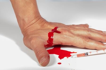 inyeccion intramuscular: Subcutánea concepto inyección médico con una pequeña jeringa hipodérmica llena de un líquido rojo que penetra en la piel y producir un flujo de sangre que gotea en una vista de primer plano
