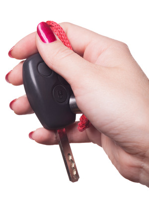 Close up of manicured hand with red nail polish holding black car key on white background Stock Photo